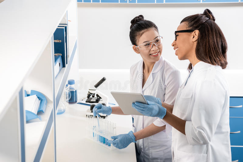 Young scientists using digital tablet while making experiment in chemical laboratory, scientists working together. Professional young scientists using digital stock photos