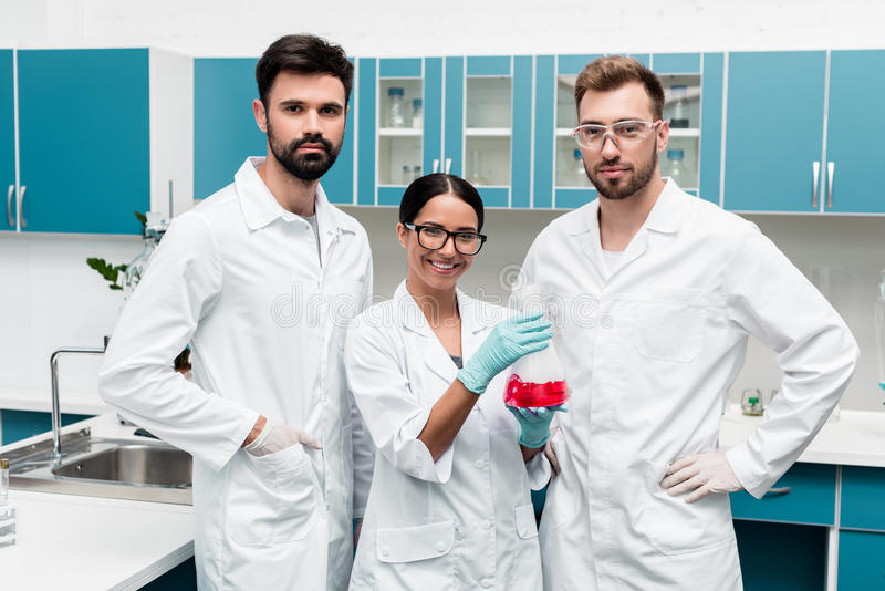Young scientists in white coats holding flask with reagent and smiling at camera in chemical lab stock images