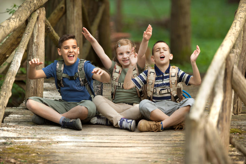 Young scouts sitting on old wooden bridge in the woods. Happy childs in green forest playing,concept of kids vacations and travel stock image