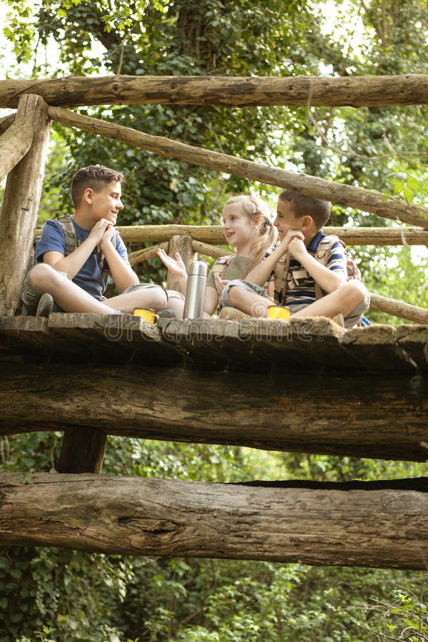 Young scouts sitting on old wooden bridge in the woods. Happy childs in green forest playing,concept of kids vacations and travel royalty free stock photo