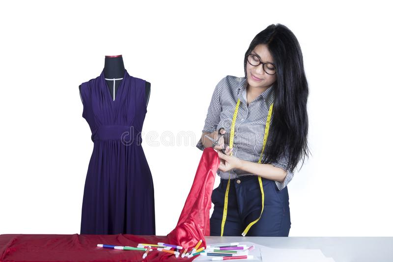 Young seamstress cutting a fabric on studio stock images