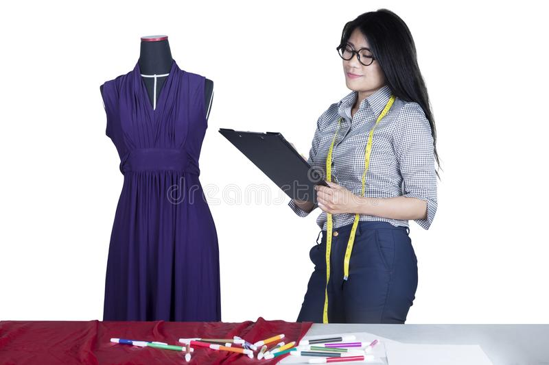 Young seamstress holding a clipboard on studio stock photo