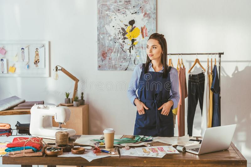 young seamstress standing at working place and looking stock photo