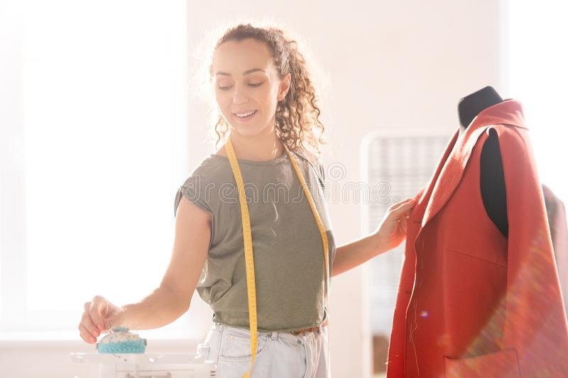 Professional seamstress. Young seamstress taking pin from workplace while standing by dummy with red unfinished coat on royalty free stock image