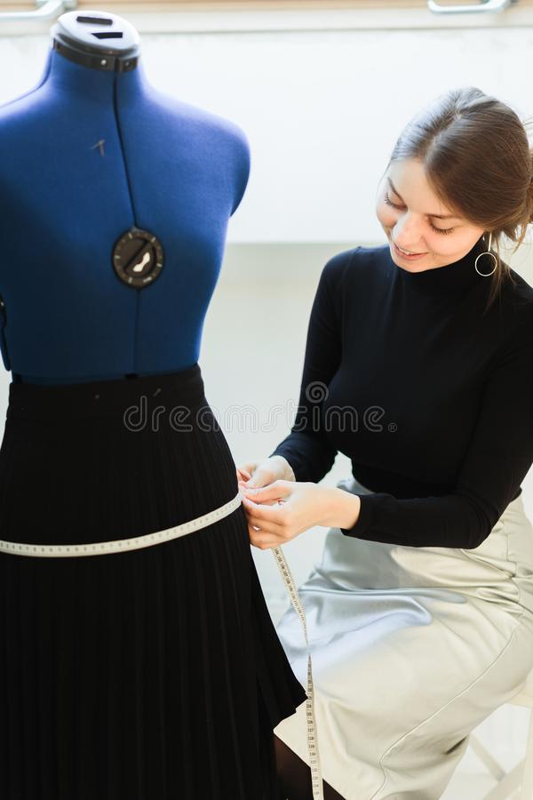 A young seamstress woman sets clothes on the mannequin royalty free stock images