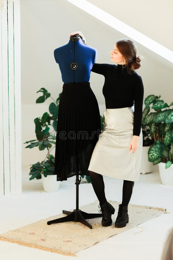 A young seamstress woman sets clothes on the mannequin royalty free stock photo