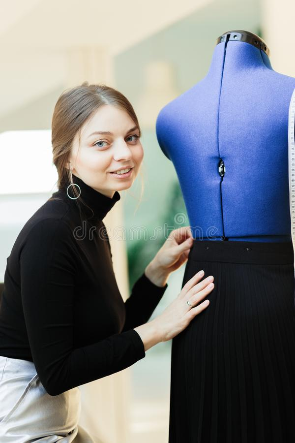 A young seamstress woman sets clothes on the mannequin stock photography