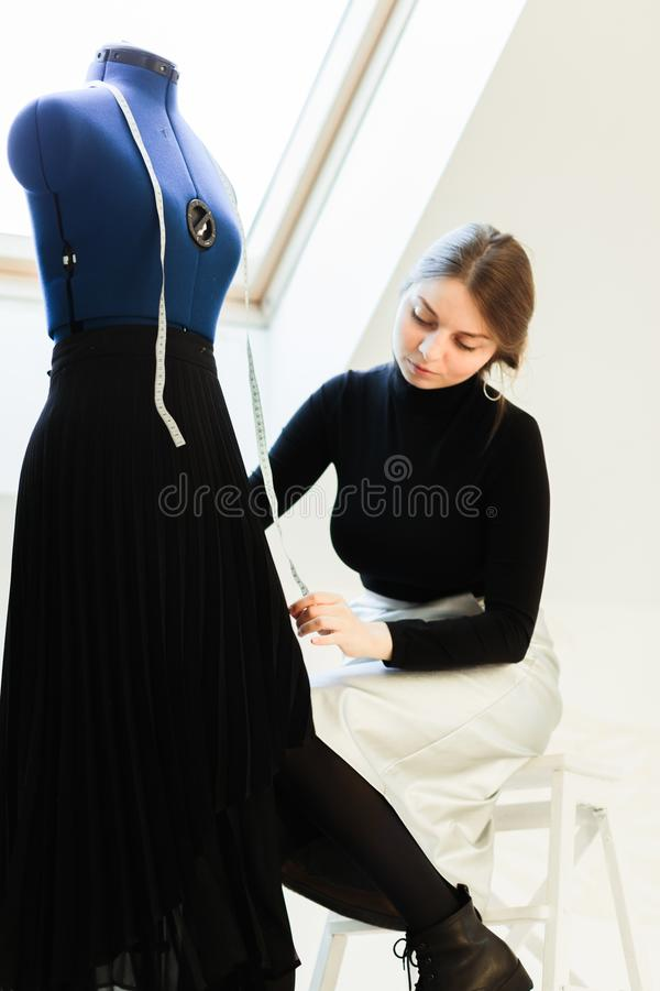 A young seamstress woman sets clothes on the mannequin stock photos
