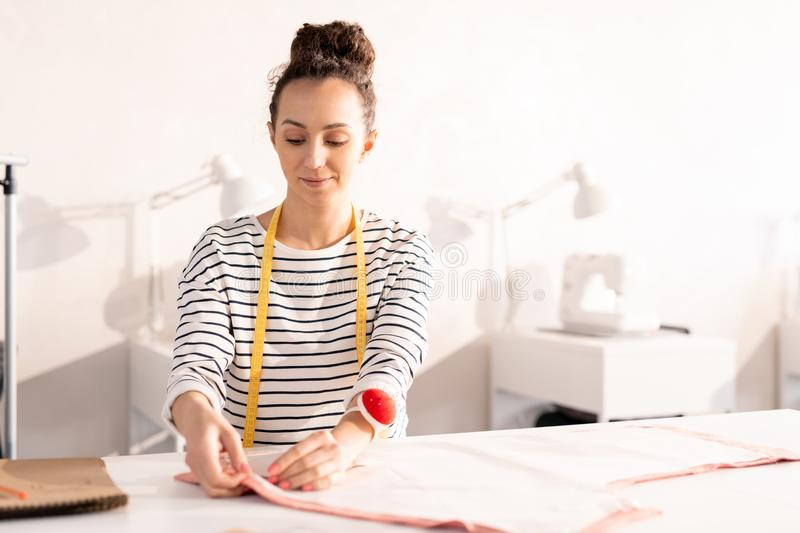 Young seamstress at work. Young seamstress or fashion designer in casualwear pinning paper pattern on piece of fabric during work over new order of client stock photography