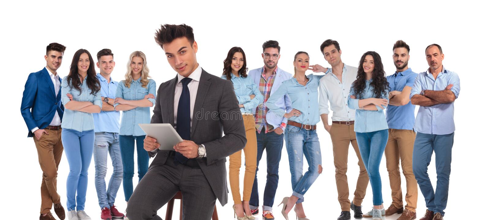 Seated businessman holding tablet in front of team royalty free stock photo