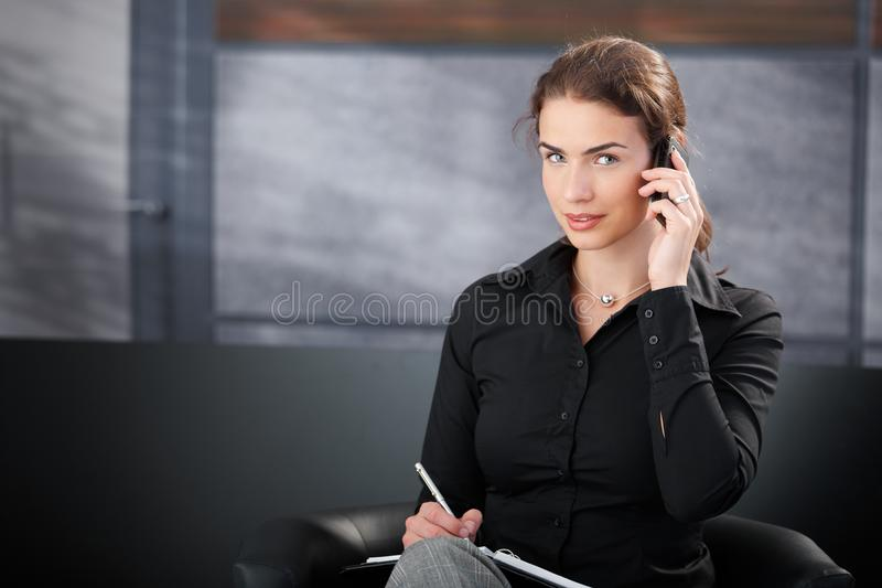 Young Secretary Talking On Cellphone Smiling Royalty Free Stock Photos