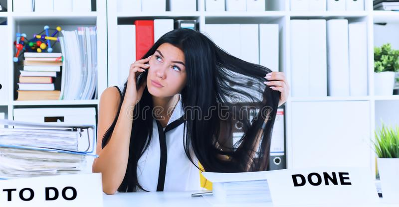 Young secretary talking on the phone forgets about a lot of paper work, which is not done. Inefficient use of working. Young beautiful secretary talking on the stock photography