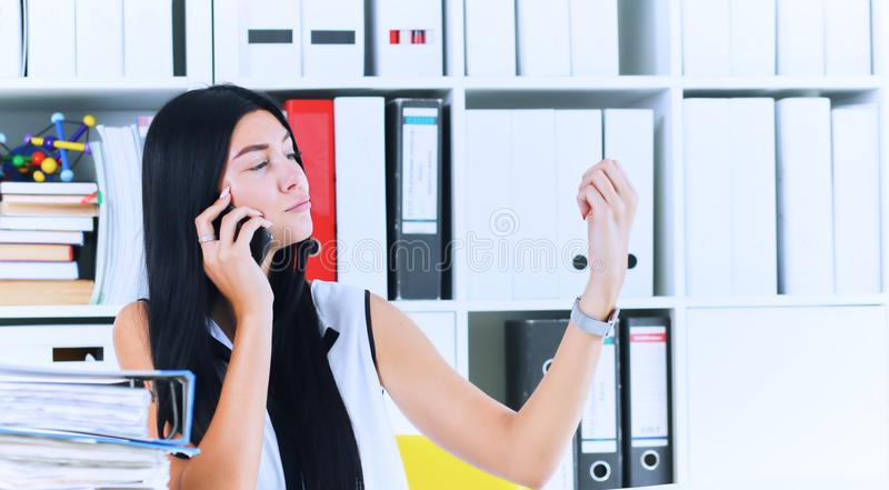 Young secretary talking on the phone forgets about a lot of paper work, which is not done. Inefficient use of working. Young beautiful secretary talking on the royalty free stock image