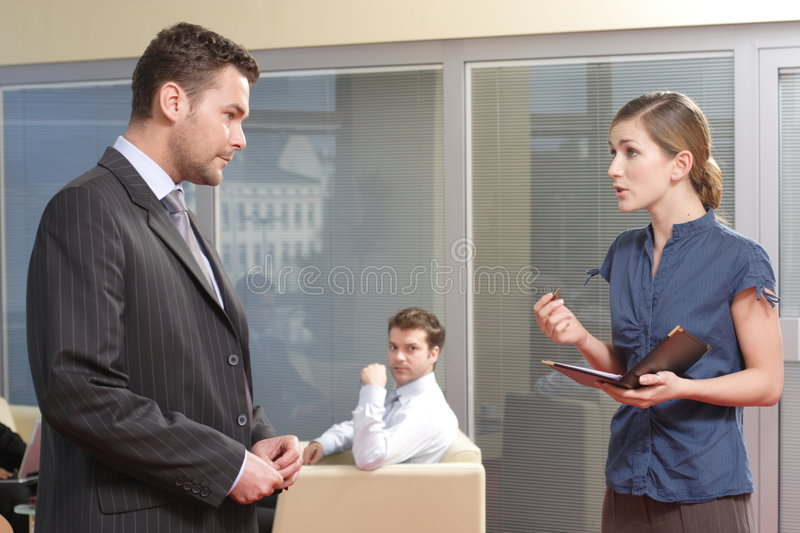 Young secretary talking to her boss in the office. Another man is observing them stock image