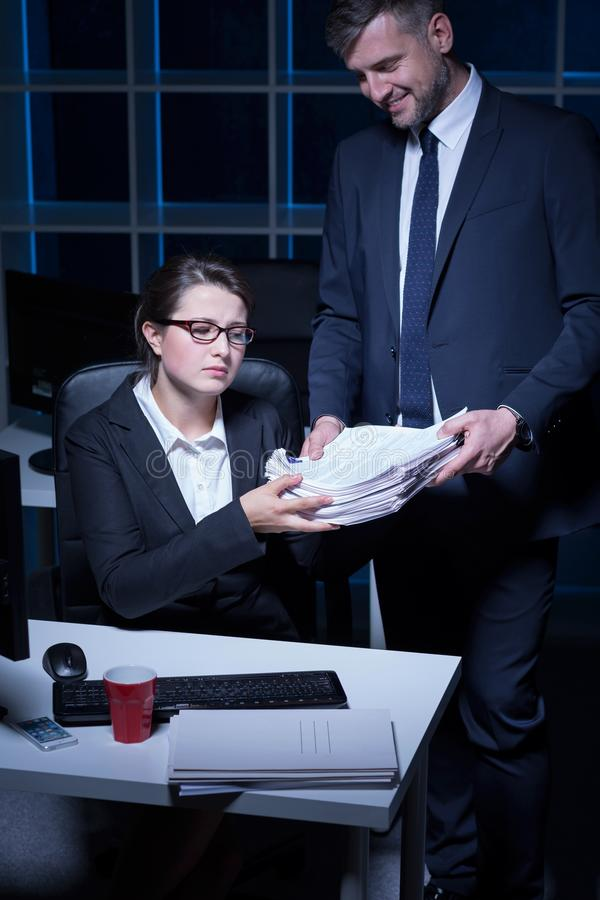 Young secretary working extra hours. In the office stock photos