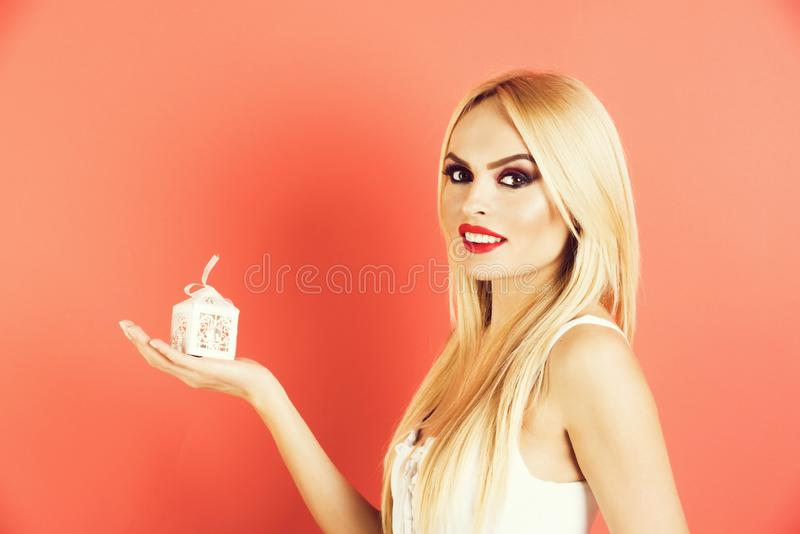 Young seductive blonde woman hold small white gift box royalty free stock photo