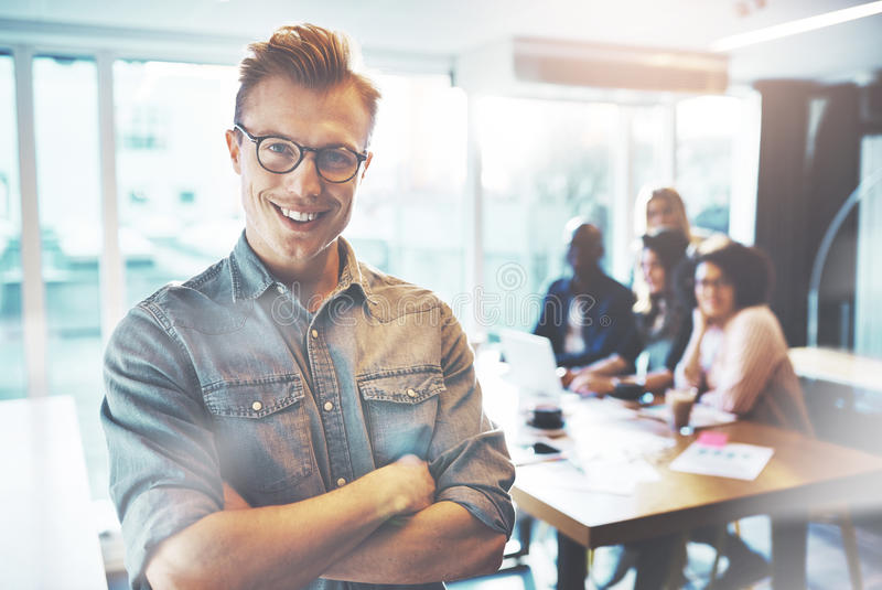 Young self confident entrepreneur posing to camera. Young self confident entrepreneur in glasses and casual clothes standing arms folded and smiling in bright stock images