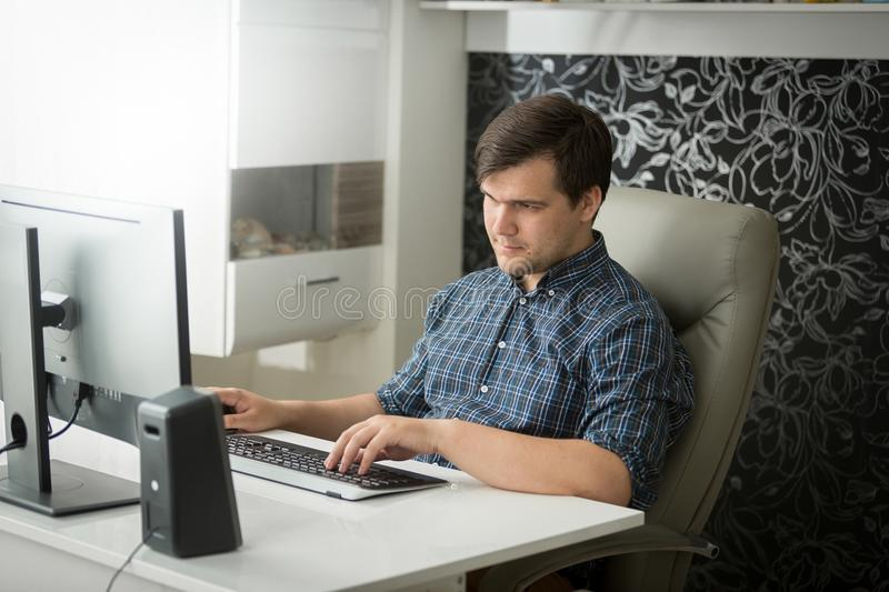 Portrait of young self-emlployed man in checkeered shirt sitting at home office and working on computer stock photo