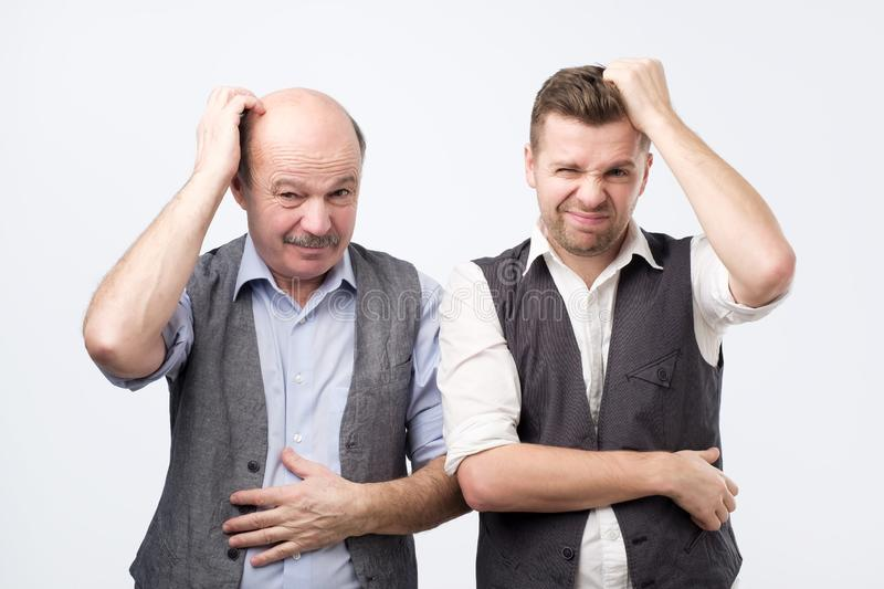 Young and senior businessman scratch their heads, confused, thinking about something stock photos