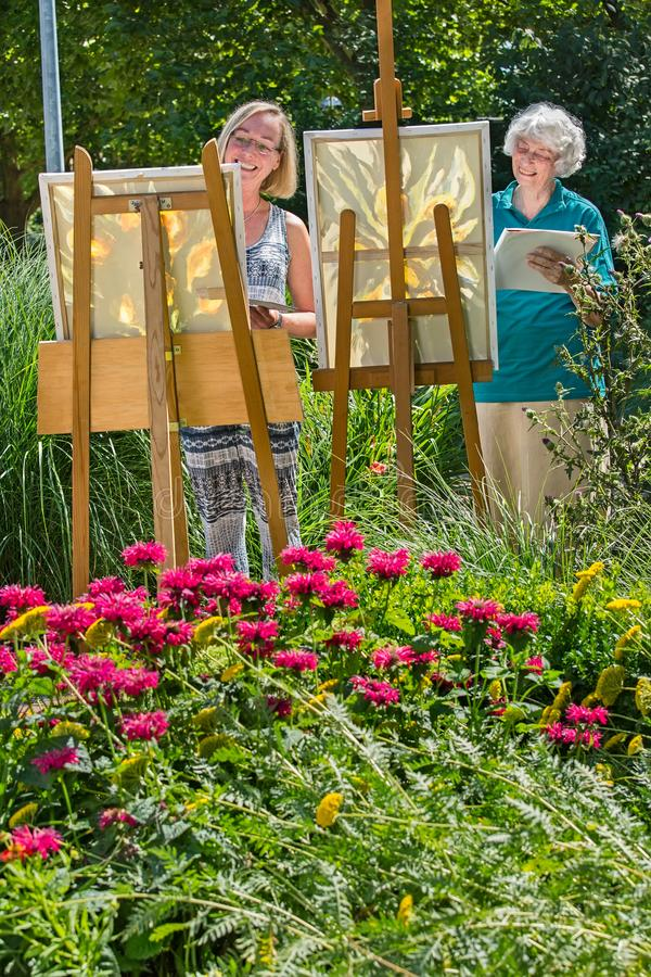 Young and senior cheerful women painting on canvas in garden during sunny day. Young and senior cheerful women painting on canvas in garden on a sunny day royalty free stock photos