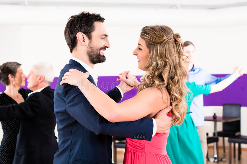 Young and senior couples getting dance stock image