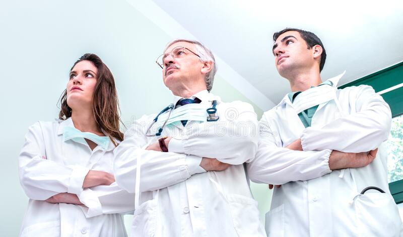 Young and senior doctors ready to fight against coronavirus outbreak at hospital clinic - Medical emergency concept stock images