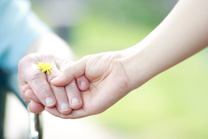 Young and senior women holding hands royalty free stock photo
