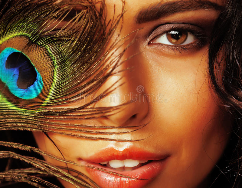 Young sensitive brunette woman with peacock feather eyes close up on green smiling, lifestyle people concept. Macro royalty free stock image