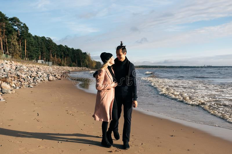 Young sensual couple having fun walking and hugging on beach. Cold autumn weather, coastline royalty free stock image