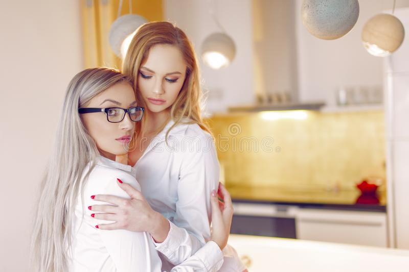 Young sensual female couple holding each other in kitchen. Lesbian lifestyle stock photos
