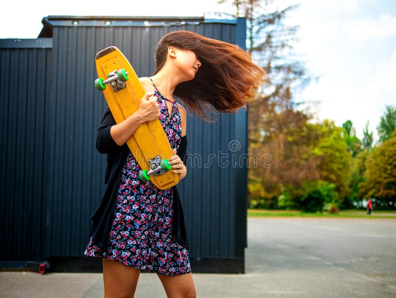 Young sensual skater girl standing in park during a beautiful sunset. stock photos