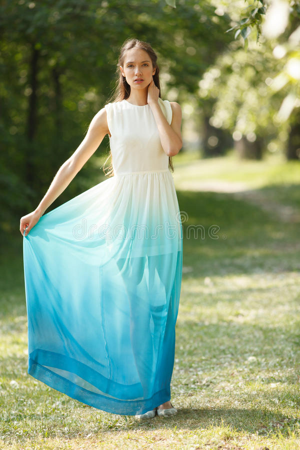 Young sensual woman. In long white and blue dress outdoors poses. Professional style stock images
