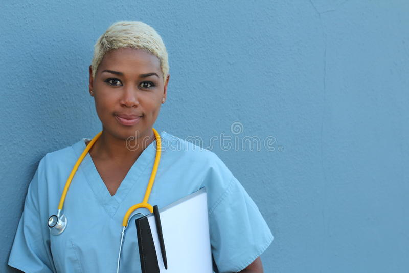 Young serious afro american nurse standing at hospital ward with clipboard and pen in hand. Neutral expression, looking at camera.  stock photos