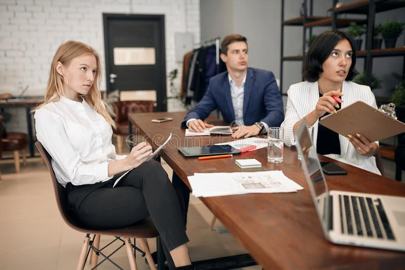 Young serious ambitious business people listening to their boss. performance royalty free stock image