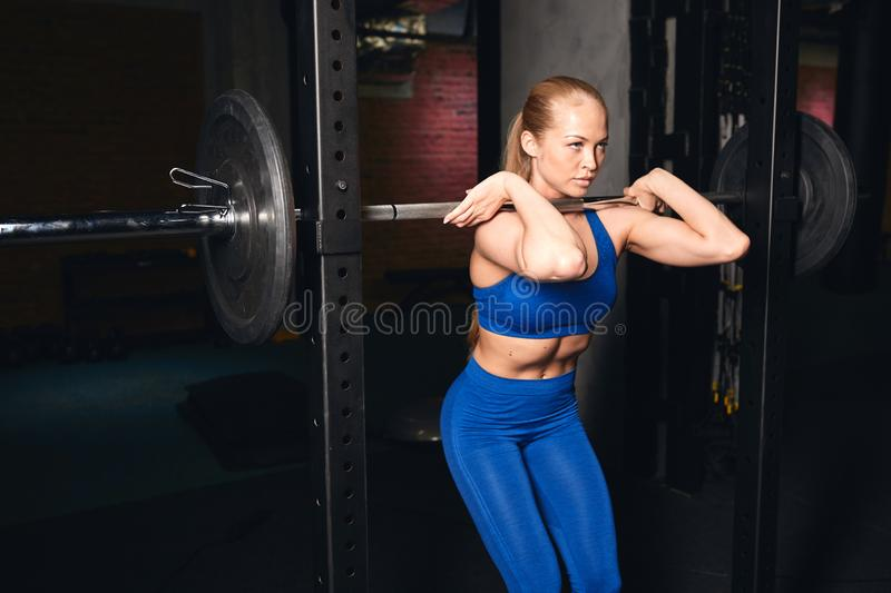 Young serious ambitious girl practising bodybuilding stock photography