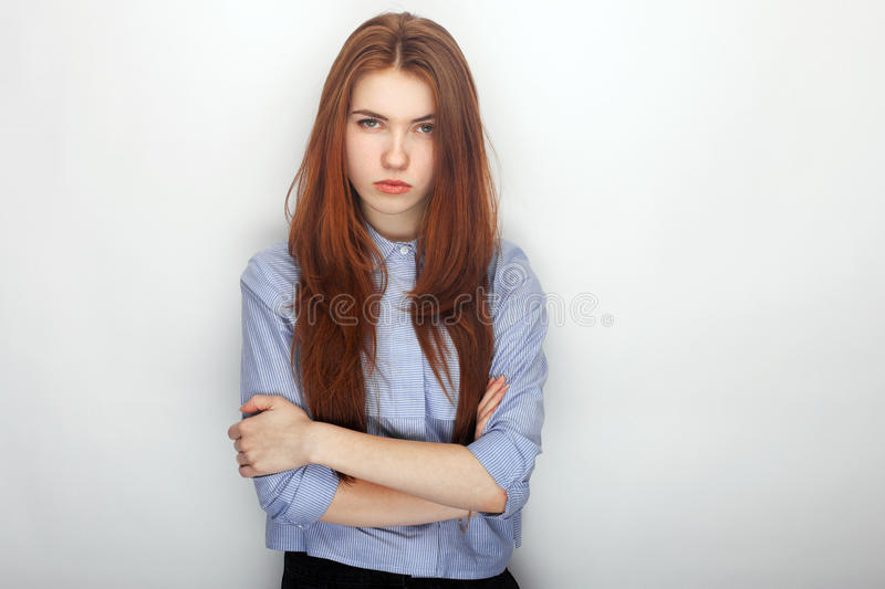 Young serious angry redhead beautiful woman in shirt portrait on a white background hugging herself royalty free stock image