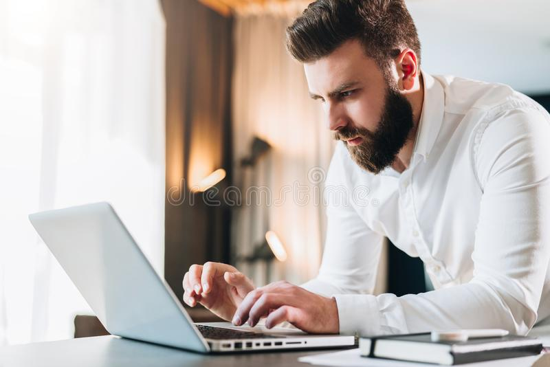 Young serious bearded businessman standing in office near table and using laptop. Man works on computer, checks e-mail stock photos