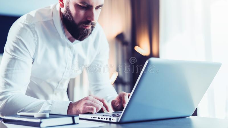Young serious bearded businessman standing in office near table and using laptop. Man works on computer, checks e-mail. Chatting, blogging. Online marketing stock images