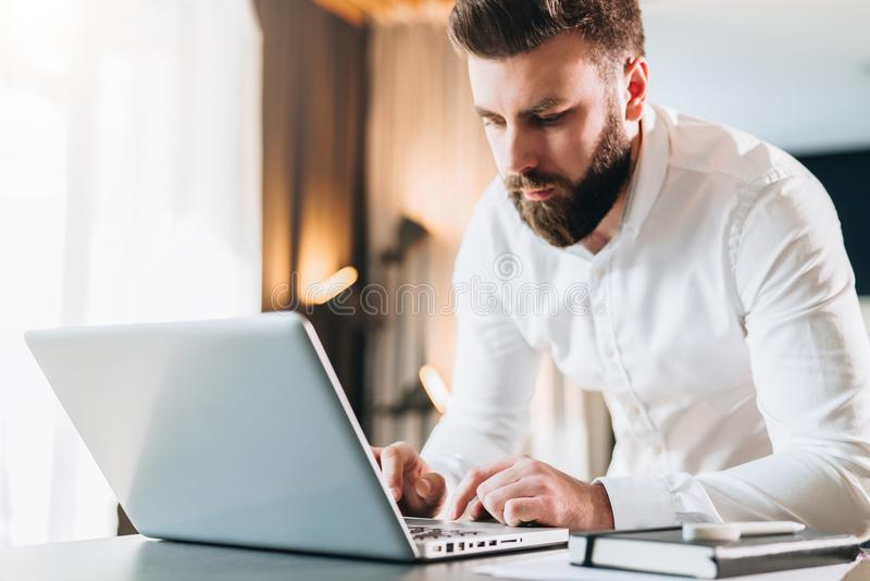 Young serious bearded businessman standing in office near table and using laptop. Man works on computer, checks e-mail. Chatting, blogging. Online marketing royalty free stock photo