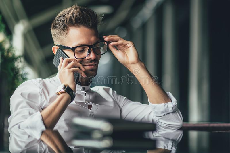 Young serious bearded businessman in white shirt is sitting in cafe at table and talking on his cell phone. Lifestyle stock images