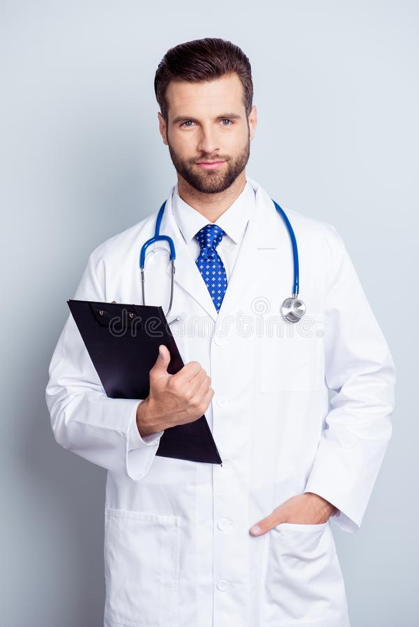 Young serious bearded intern in uniform and a tie is standing on. The white background, he is holding the black clipboard royalty free stock photography