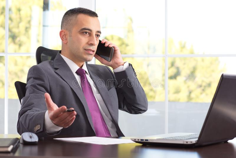 Young And Serious Boss Or Businessman Talking On The Phone royalty free stock images