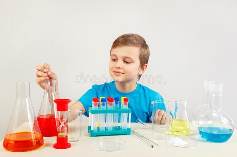 Young serious boy doing chemical experiments in laboratory. Young serious boy doing chemical experiments in the laboratory royalty free stock photos