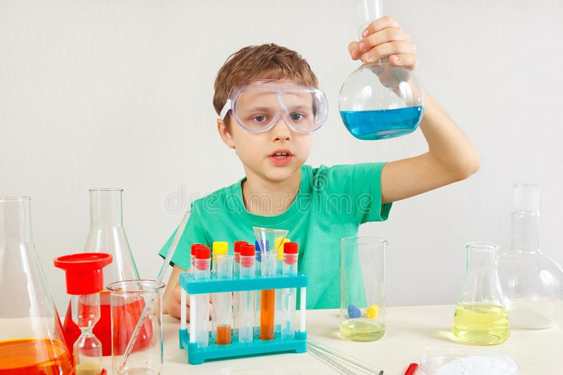 Young serious boy in safety goggles doing chemical experiments in laboratory. Young serious boy in safety goggles doing chemical experiments in the laboratory stock photo