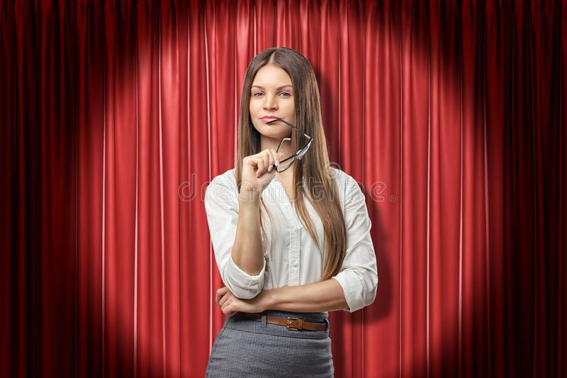 Young serious brunette business woman with glasses thinking on red stage curtains background royalty free stock photo