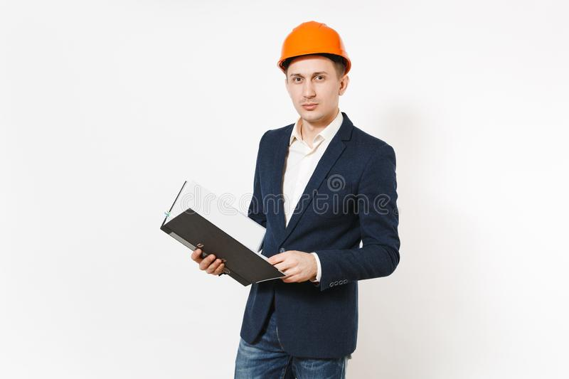 Young serious businessman in dark suit, protective construction orange helmet holding black folder for papers document stock photography