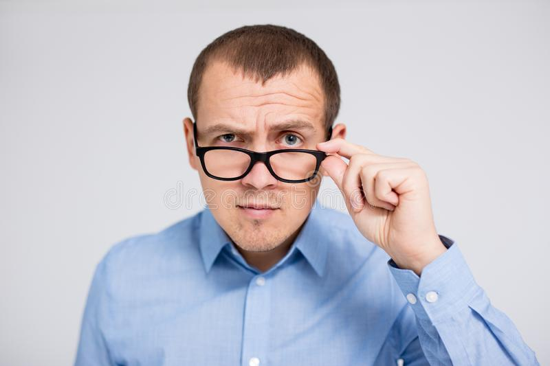 Young serious businessman in eyeglasses looking at camera over gray background royalty free stock photography