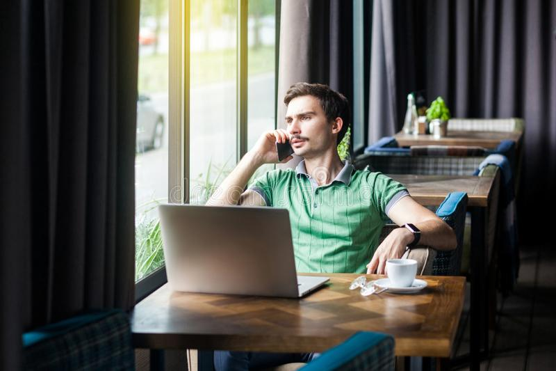 Young serious businessman in green t-shirt sitting at desk with laptop, talking on phone and looking outside. business and royalty free stock photography