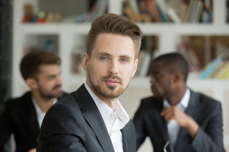 Young serious businessman looking at camera on meeting, headshot royalty free stock photo