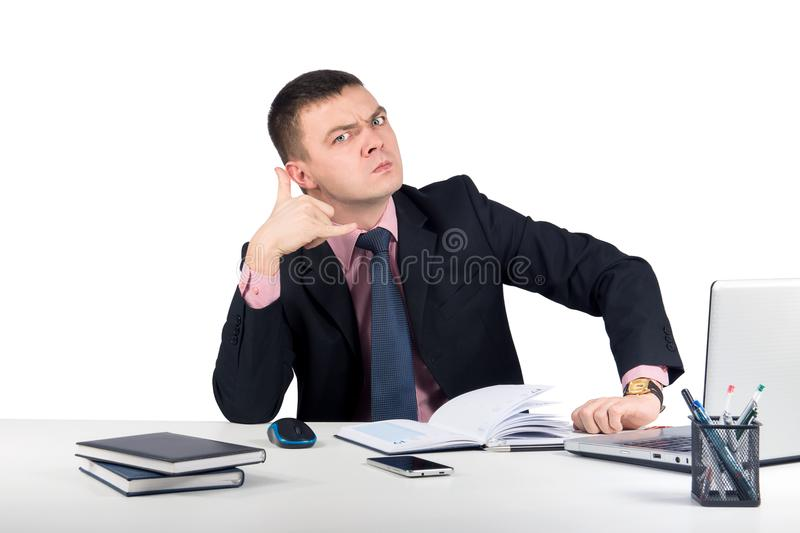 Young serious businessman shows `call me royalty free stock image